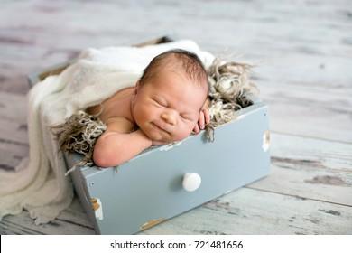 Newborn baby boy, sleeping happily in basket