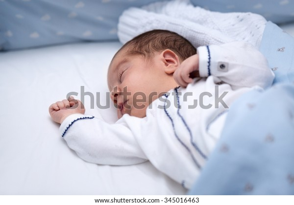 Newborn baby boy sleeping in his bed. Newborn Sleep. Two days old in maternity