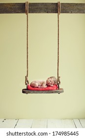 Newborn baby boy sleeping on an antique swing