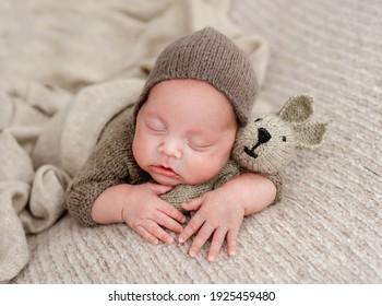 Neugeborener, der auf Strickspielzeug schläft. Kleinkind mit braunem Anzug auf beigem Hintergrund