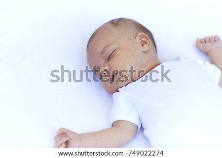 Newborn baby boy sleeping on back on a white blanket