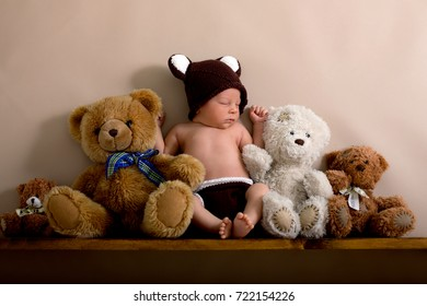 Newborn baby boy wearing a brown knitted bear hat and pants, sleeping on a shelf next to Teddy Bears. Shot in the studio on a creamy background, shot from above