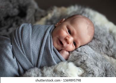 newborn baby boy in wrap sleeping on fur