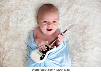 Newborn baby boy, wrapped in blue scarf, holding a little guitar and smiling