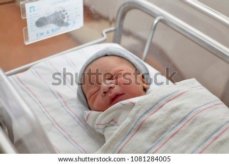 A newborn baby boy wrapped in a hospital blanket laying in the hospital crib with eyes closed