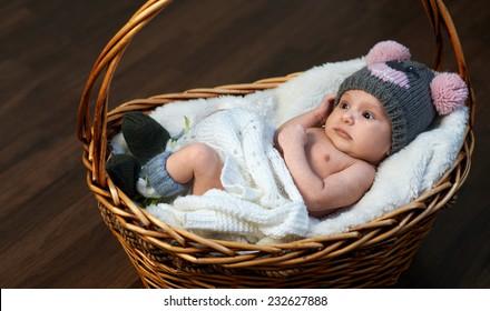 newborn baby in the cap in the basket on the floor