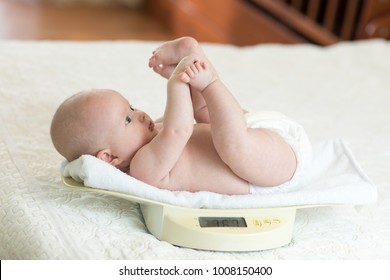 Newborn baby child on weighing scale indoors