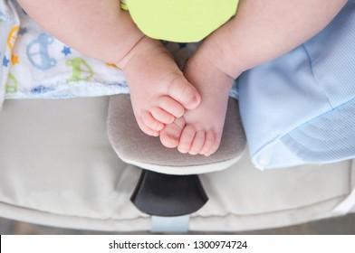 Newborn baby chubby feet over on i-size baby car over pushchair. Overhead shot