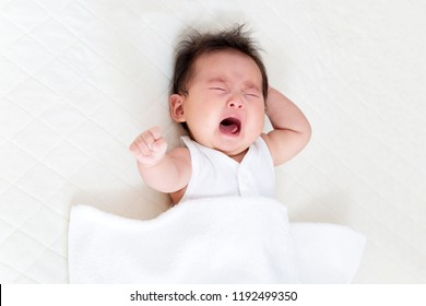 A newborn baby cried lying on a white sheet. Newborn baby, baby, child care, growth, health image