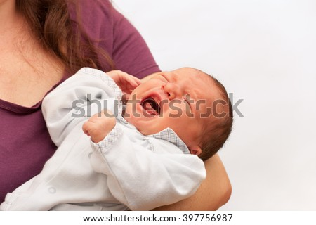 Newborn baby crying in his mother's arms