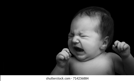 Newborn baby crying. Baby on black background. Black and white photo. Baby's portrait in low key
