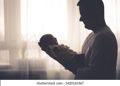 newborn baby and dad, a newborn baby in her husband's arms, a baby in a man's arms. Dad and son, fatherhood concept. Real room, dark style and toning