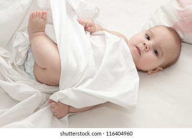 Newborn baby in diapers lying in bed on white sheets covered with white blanket.