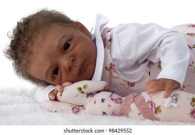 A newborn baby Doll Lying Down with Bunny Toy, Isolated on White