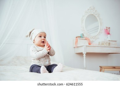 Newborn baby dressed in a suit on a soft bed in the studio