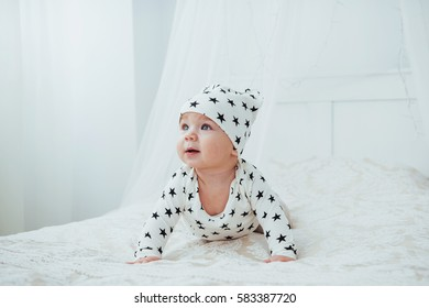 Newborn baby dressed in a white suit and black stars is a white soft bed in the studio.