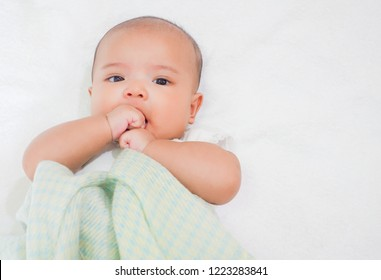 Newborn baby eat her thumb on white towel background and light green warm woolen blanket
