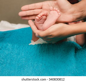 Newborn baby feet in mother hands closeup