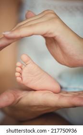Newborn baby feet in mother hands.Masseur massaging little baby's foot, shallow focus. Newborn baby feet in mother's hands.Mother making massage of child's foot