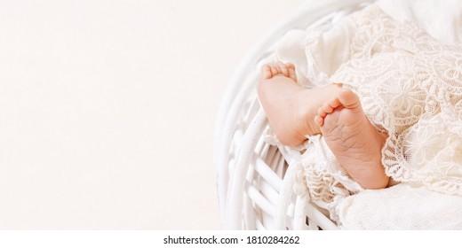 Newborn baby feet on openwork plaid. Closeup picture. Tiny newborn baby's feet  closeup. Copy space. Banner