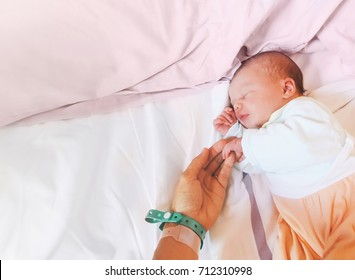Newborn baby first days of life in delivery room. Infant asleep in hospital after childbirth. New born and his mother with name tag bracelets.