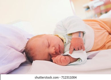 Newborn baby first days of life in delivery room. Infant asleep in hospital after childbirth. New born close-up with name tag bracelet.