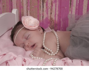 Newborn baby girl asleep in her bed. She is wearing a beautiful pink flowered headband, pearls, and a gray tutu.
