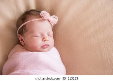 Newborn baby girl asleep on a blanket. Close-up