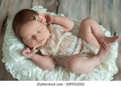 Newborn baby girl in bandage bow sleeping in wicker basket on plaid shawl on beige wooden floor.
