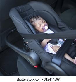 A newborn baby girl in a car seat.