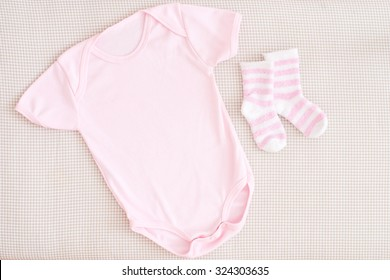 newborn baby girl clothes - studio shot from above isolated little pink body and striped socks on natural background