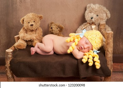 Newborn baby girl dressed as Goldilocks and sleeping on a rustic wooden bed surrounded by three plush toy bears.