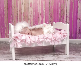 Newborn baby girl with feathered halo and wing's asleep in her bed she look's like and angel.