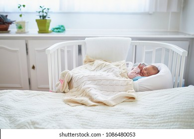 Newborn baby girl having a nap in co-sleeper crib attached to parents' bed