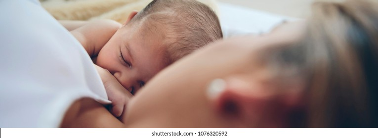 Newborn baby girl lying on the bed embraced by her mother. Selective focus on baby in background