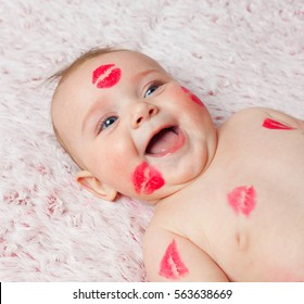 4f2b886af9d8 Newborn baby girl on the soft blanket filled kisses made with the lipstick.