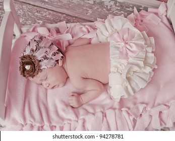 Newborn baby girl one week old asleep in her bed with with bloomers and a pink bow and a feathered headband.