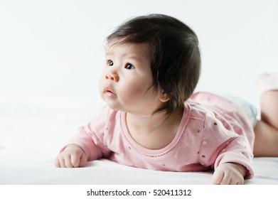 newborn baby girl in pink dress on white background