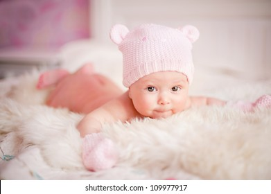 7860ebb6aac9e newborn baby girl in pink knitted bear hat lies at fur
