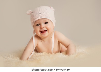 Newborn baby girl in pink knitted cap the mouse on the bed