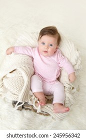 Newborn baby girl posed in a bowl on her back, on knit blanket, smiling looking at camera, wearing comfortable pj pajamas
