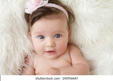 Newborn baby girl posed in a bowl on her back, on blanket of fur, smiling looking at camera