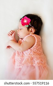 newborn baby girl is sleeping, dressing pink cloths, which looks like  skirt, with   headdress