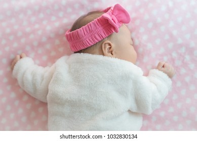 Newborn baby girl sleeping on a bed