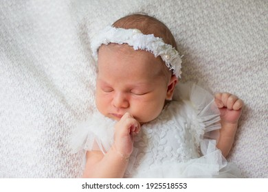 Newborn baby girl sleeping on a white blanket in a dress and wreath
