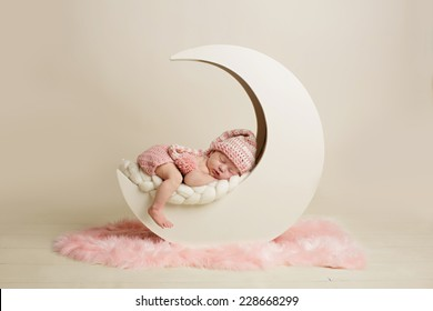 Newborn baby girl sleeping on the moon