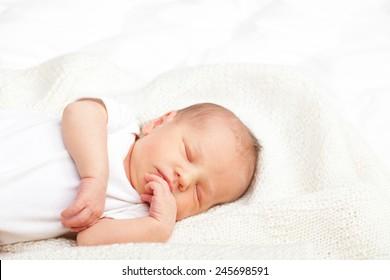 Newborn baby girl sleeping on a white blanket