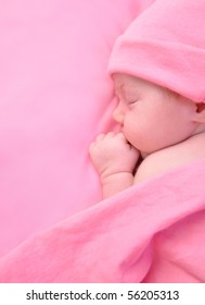 A newborn baby girl is sleeping on a pink blanket and is wearing a hat. Use it for a childhood, parenting  or innocence theme. Add your text message to the side.