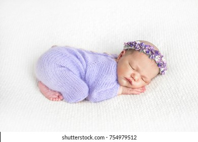 Newborn. Newborn baby. A baby girl is sleeping on a light bed. A newborn baby girl in a wreath and a light woolen suit of purple is sleeping on a light-colored blanket. Pose of the baby.