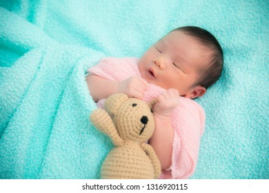 Newborn baby girl sleeping together with teddy bear